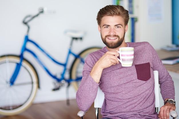 Bicicleta azul ao lado de homem alegre