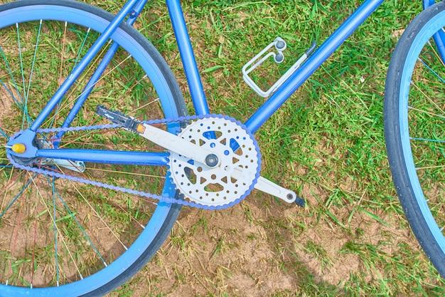 Bicicleta azul brilhante deitada na grama com areia em um dia ensolarado