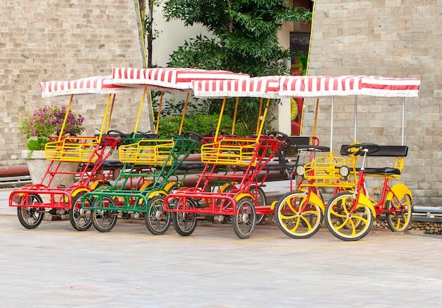 Bicicleta com quatro rodas na praça.