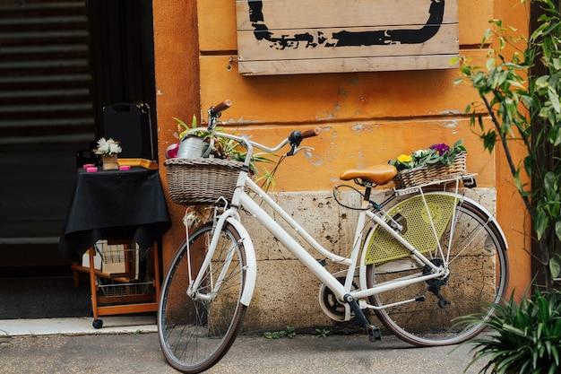Bicicleta com uma cesta de flores ao lado de um café moderno, ruas bonitas de pequenos vilarejos italianos