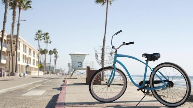 Bicicleta cruiser bike pela praia do oceano, costa da califórnia, eua. ciclo de verão, cabana do salva-vidas e palmeira