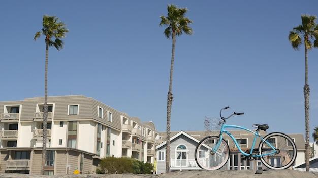 Bicicleta cruiser bike pela praia do oceano, costa da califórnia, eua. ciclo de verão, casas e palmeiras.