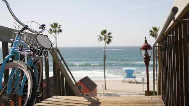 Bicicleta cruiser bike pela praia do oceano, costa da califórnia, eua. ciclo de verão, escadas e palmeiras.