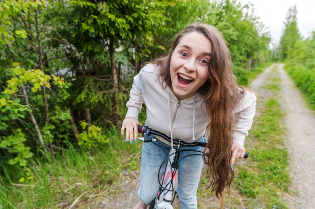 Bicicleta da equitação da jovem mulher no parque da cidade do verão fora.