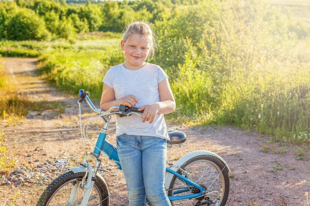 Bicicleta de equitação criança feliz. moça na bicicleta no parque ensolarado do verão. atividade saudável de verão crianças em idade escolar. crianças brincando e andando de bicicleta ao ar livre