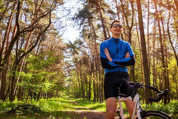 Bicicleta de equitação jovem ciclista na floresta de primavera. homem descansando