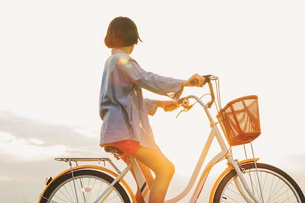 Bicicleta de equitação jovem mulher asiática no parque com pôr do sol
