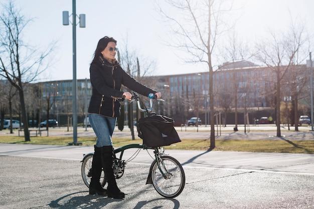 Bicicleta de equitação mulher moderna na cidade