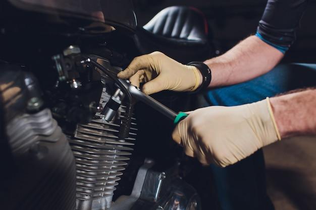 Bicicleta de fixação do homem. homem novo seguro que repara a motocicleta perto de sua garagem.