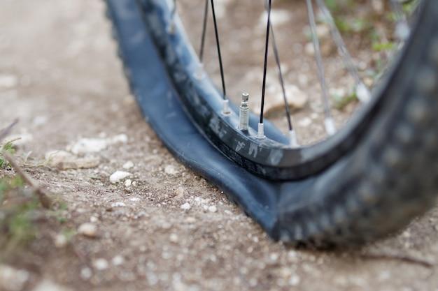Bicicleta de montanha com pneu furado na trilha. foco seletivo.