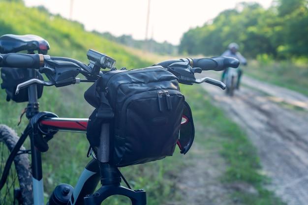 Bicicleta de montanha com um saco no guiador no fundo dos motociclistas.