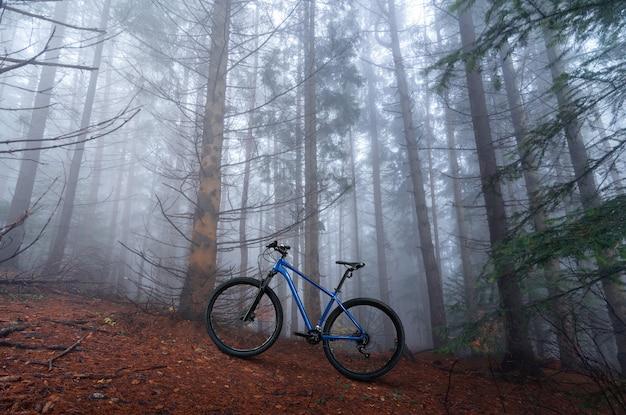 Bicicleta de montanha cross country em pé na floresta nebulosa de outono. conceito de atividade ao ar livre. ciclismo offroad.