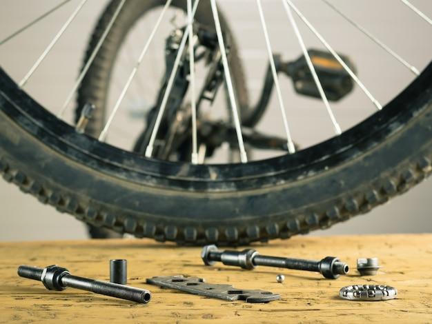 Bicicleta de montanha e ferramentas da roda traseira em uma tabela de madeira.