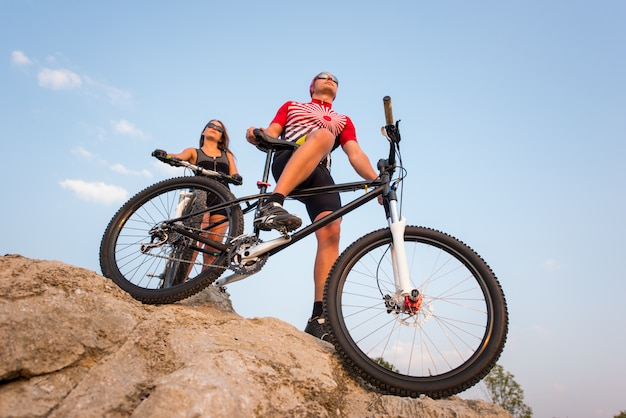 Bicicleta de montanha e piloto contra o céu azul