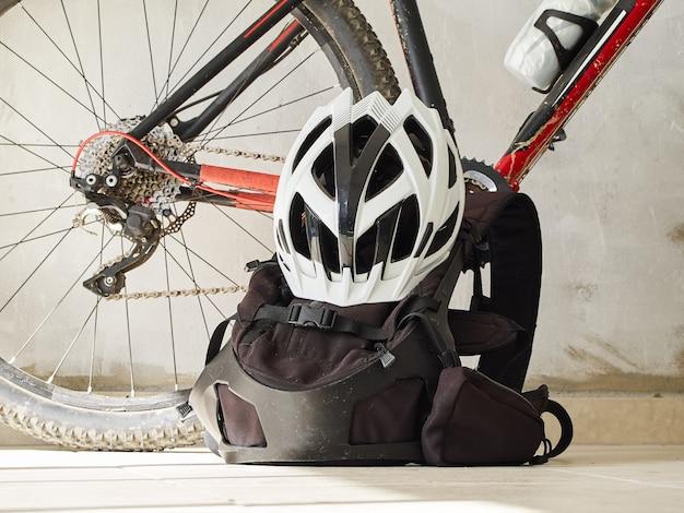 Bicicleta de montanha, mochila e capacete em uma garagem. equipamento de mountain bike. estilo de vida esportivo.