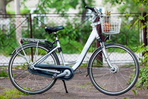 Bicicleta de mulher cidade branca com um abacaxi na cesta no ensolarado da