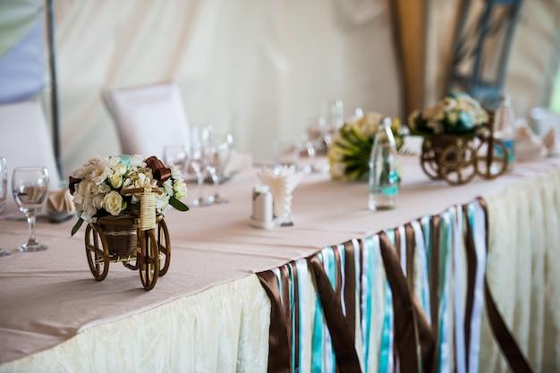 Bicicleta de vime pequena com cesta e flores como parte das decorações de casamento