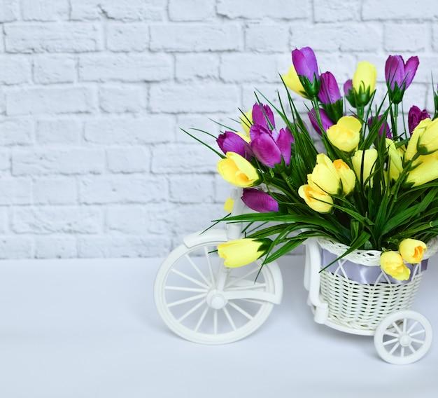 Bicicleta decorativa bonita pequena com as flores amarelas e roxas em um fundo branco.