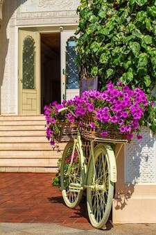 Bicicleta decorativa com flores em pé na frente do prédio