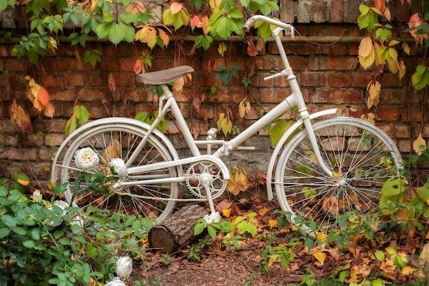 Bicicleta decorativa estacionada contra uma parede de tijolos no jardim. decoração de quintal. canto com jardim de outono.