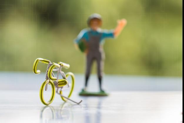 Bicicleta e miniatura agricultor pessoas em pé idéias para salvar o planeta