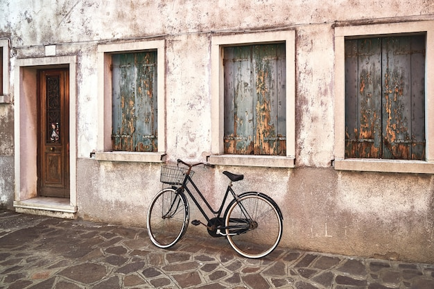 Bicicleta enferrujada velha contra o velho muro na rua. itália, veneza, ilha de burano