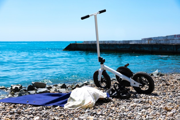 Bicicleta esportiva na cor branca, a scooter fica estacionada na praia. foco seletivo.
