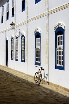 Bicicleta estacionada ao lado da parede branca com janelas azuis