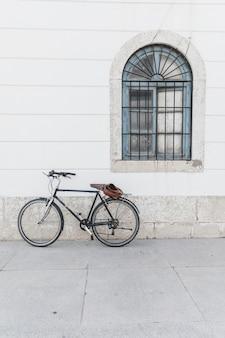 Bicicleta estacionada na parede branca com janela