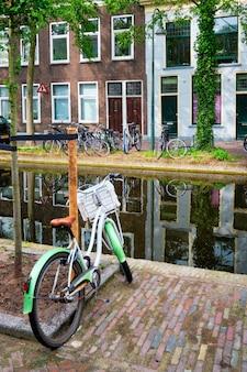 Bicicleta estacionada perto do canal na rua delft com casas antigas delft holanda