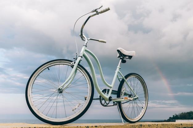Bicicleta feminina vintage no fundo do mar e um arco-íris