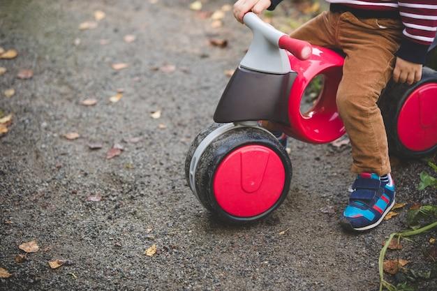 Bicicleta infantil de plástico moderna com o menino no parque