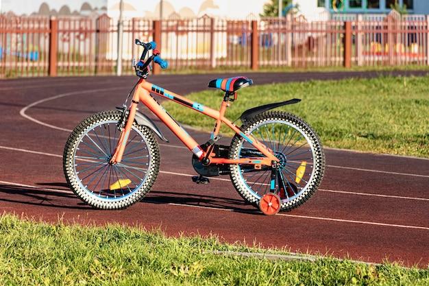 Bicicleta infantil na pista de esportes. bicicleta de equilíbrio para crianças. ensinar uma criança a praticar esportes.