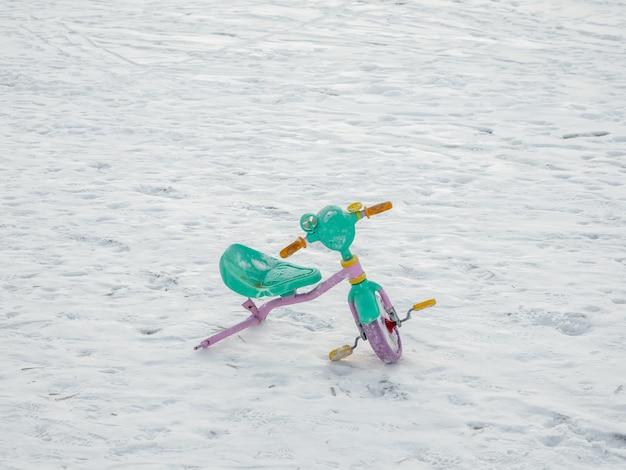 Bicicleta infantil quebrada abandonada na neve. o fim do conceito de férias.