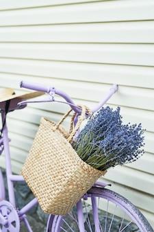 Bicicleta lilás com uma cesta de lavanda no quintal