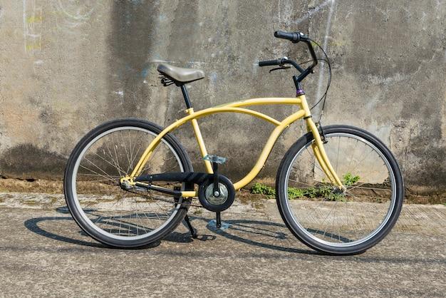 Bicicleta na rua com parede cinza