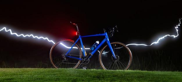 Bicicleta no gramado à noite com uma faixa de luz.