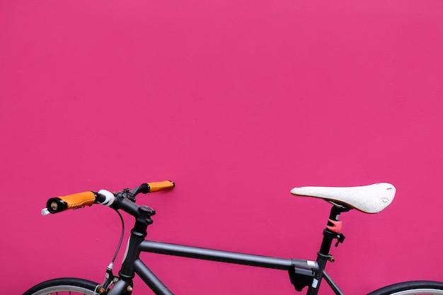 Bicicleta por uma parede fúcsia