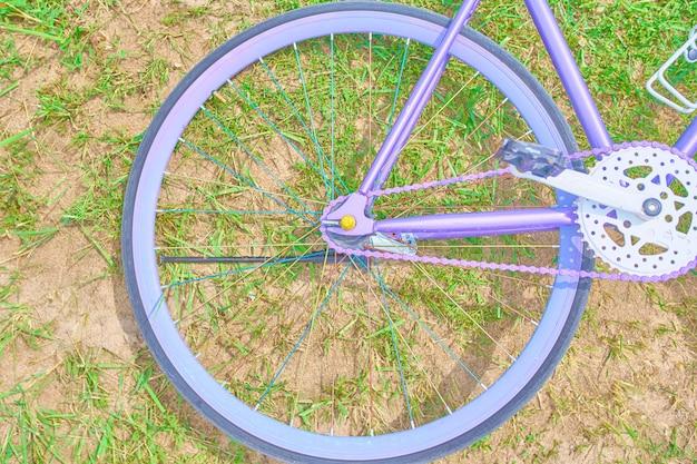 Bicicleta roxa saturada deitado na grama com areia em um dia ensolarado