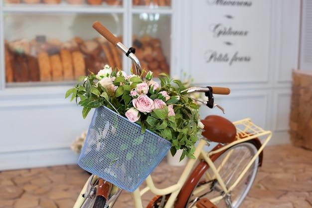 Bicicleta velha com uma cesta de rosas contra a parede em tons pastel. suporte de bicicleta decorativo para plantas e flores.