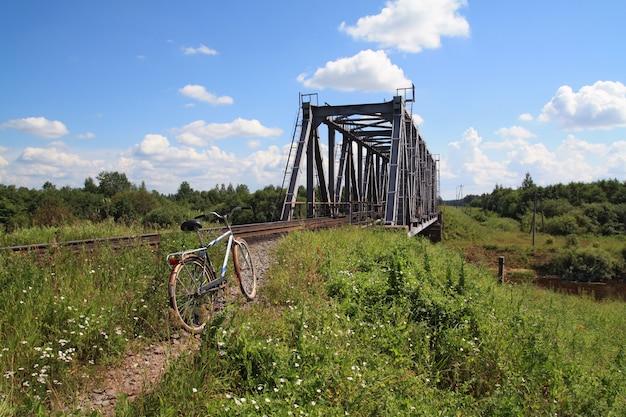 Bicicleta velha perto da ponte ferroviária