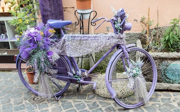 Bicicleta violeta vintage com flores e laços