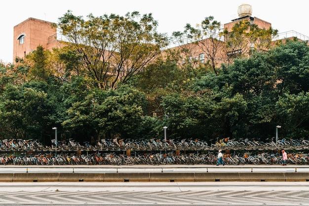Bicicletários na calçada em frente à universidade nacional de taiwan com pessoas caminhando