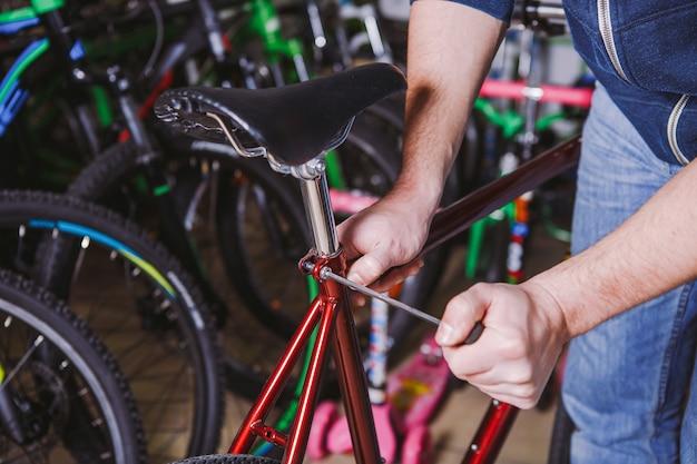 Bicicletas de reparo temático. close da mão de um homem caucasiano com as teclas hexagonais de uma ferramenta manual para ajustar e instalar os espigões de selim prateados em uma bicicleta vermelha.