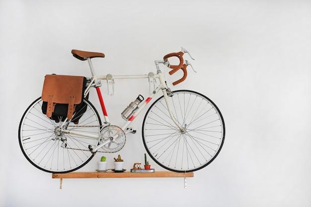 Bicicletas decorativas que penduram na parede branca.