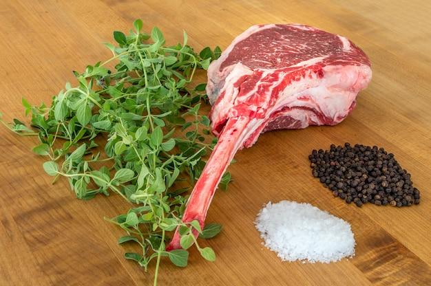 Bife angus tomahawk cru em uma placa de madeira com sal, pimenta, orégano e uma faca