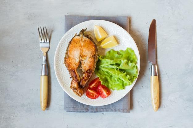 Bife assado peixe salmão em um prato com legumes frescos.