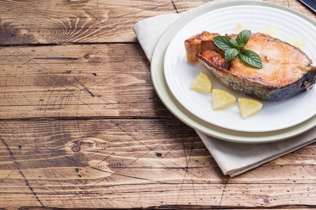 Bife assado peixe salmão em um prato com limão. mesa de madeira.