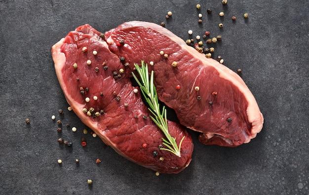 Bife, carne crua com especiarias e alecrim em um fundo preto de concreto. vista de cima.