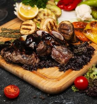 Bife club com molho de pimenta e legumes grelhados na tábua de cortar